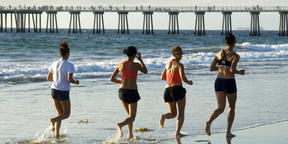 four women are seen jogging along the waters edge for exercise.